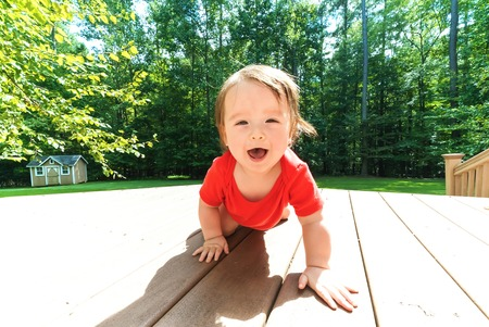 Photo pour Happy toddler boy crawling and playing outside - image libre de droit