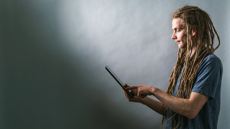 Foto de Young man using his tablet on a dark gray background - Imagen libre de derechos
