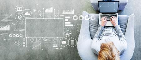 Foto de Marketing concept with man using a laptop in a modern gray chair - Imagen libre de derechos