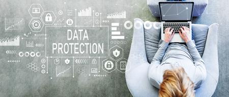 Foto de Data protection with man using a laptop in a modern gray chair - Imagen libre de derechos