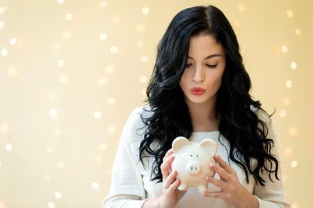 Photo pour Young woman with a piggy bank on a shiny lights background - image libre de droit