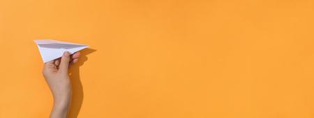 Foto de Woman holding a paper air plane on a orange background - Imagen libre de derechos
