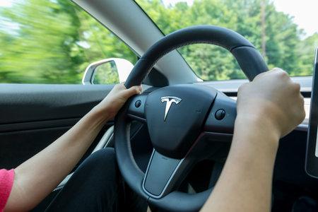 Foto de RALEIGH, NC - JUNE 08, 2018: Man driving an all electric Tesla Model 3. The Model 3 is set to be the Teslas first mass market electric vehicle. - Imagen libre de derechos