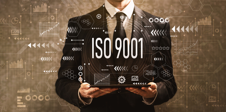Foto de ISO 9001 with businessman holding a tablet computer on a dark vintage background - Imagen libre de derechos