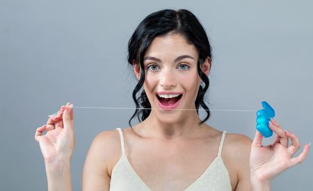 Foto de Young woman with dental floss on a gray background - Imagen libre de derechos