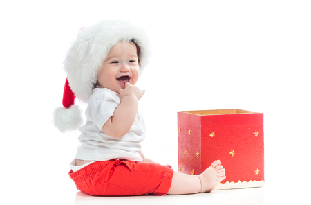 Photo for Happy baby boy with a Santa hat with a Christmas present box - Royalty Free Image
