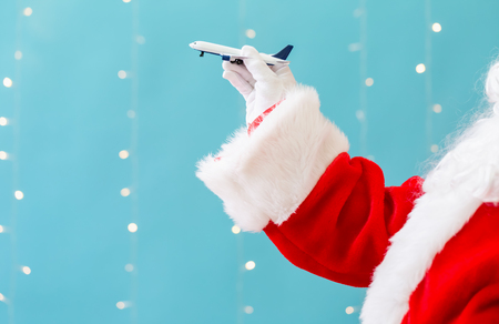 Photo for Santa holding a toy airplane on a shiny light blue background - Royalty Free Image