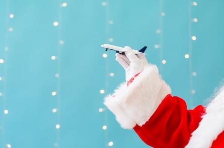 Foto de Santa holding a toy airplane on a shiny light blue background - Imagen libre de derechos