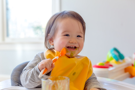 Photo for Happy toddler boy smiling while eating a meal - Royalty Free Image