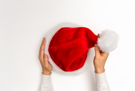 Photo for Hand holding a Santa hat on a white background - Royalty Free Image