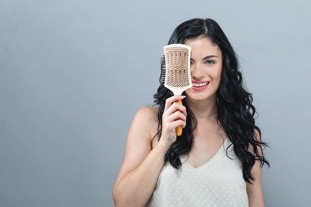 Photo pour Beautiful young woman holding a hairbrush on a gray background - image libre de droit