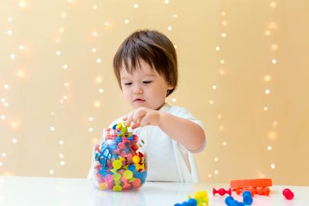 Photo pour Little toddler boy playing with his toys - image libre de droit