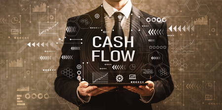 Foto de Cash flow with businessman holding a tablet computer on a dark vintage background - Imagen libre de derechos