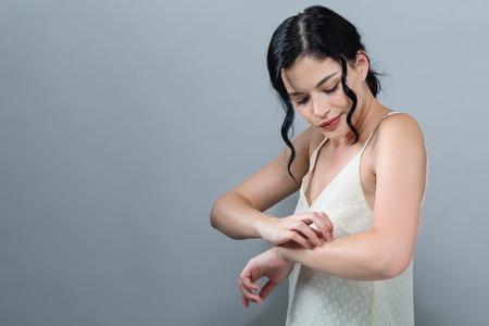 Foto de Young woman scratching her itchy arm. Skin problem. on a gray background - Imagen libre de derechos