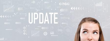 Foto de Update with young woman looking upwards on a gray background - Imagen libre de derechos
