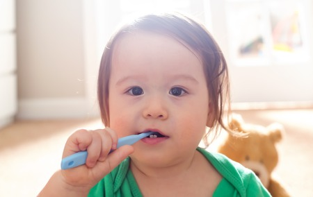 Photo pour Toddler boy brushing his teeth with a toothbrush - image libre de droit