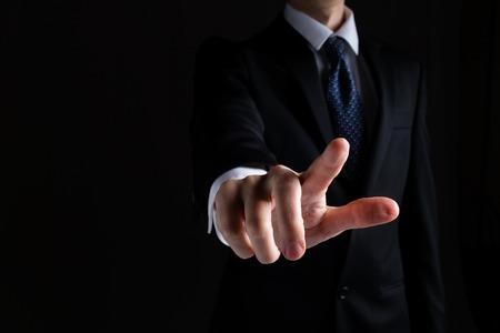 Foto de Man in a suit pointing or pressing something on black background - Imagen libre de derechos