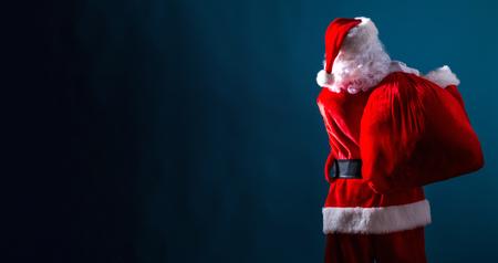 Foto de Santa holding a red sack on a dark blue background - Imagen libre de derechos