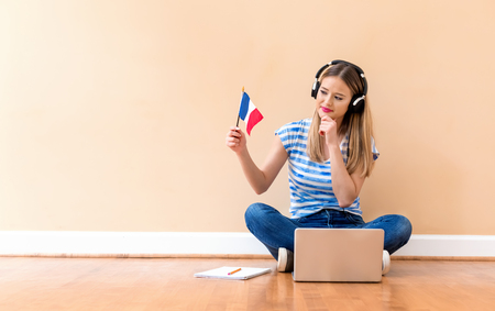 Photo pour Young woman with French flag using a laptop computer against a big interior wall - image libre de droit