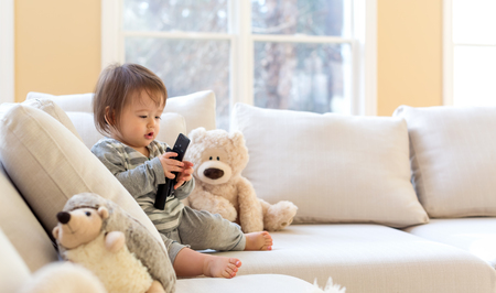 Photo for Little toddler boy with a TV remote control - Royalty Free Image