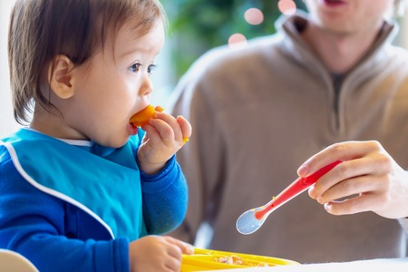 Photo pour Toddler boy eating food in the kitchen - image libre de droit