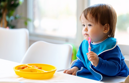 Foto de Toddler boy eating food in the kitchen - Imagen libre de derechos