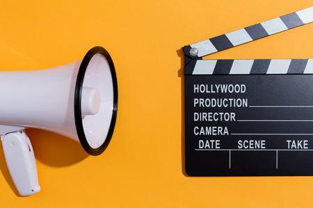 Photo pour Movie slateboard clapper with megaphone on a orange background - image libre de droit