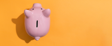 Foto de A piggy bank saving and investment theme on a orange background - Imagen libre de derechos