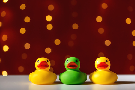 Photo for Rubber duck toys on a shiny light dark red background - Royalty Free Image