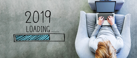 Foto per Loading new year 2019 with man using a laptop in a modern gray chair - Immagine Royalty Free