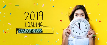 Photo pour Loading new year 2019 with young woman holding a clock showing nearly 12 - image libre de droit