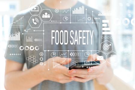 Foto de Food safety with young man using a smartphone - Imagen libre de derechos