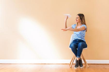 Foto de Young woman with a paper airplane in a chair - Imagen libre de derechos