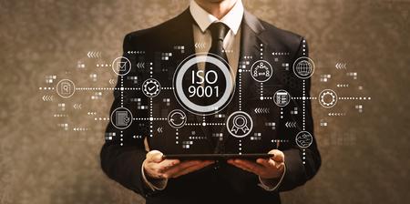 Foto de ISO 9001 with businessman holding a tablet computer on a dark vintage background - Imagen libre de derechos
