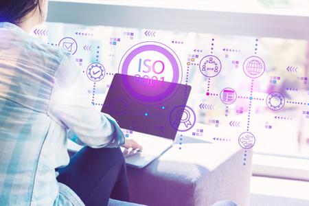 Foto de ISO 9001 with woman using her laptop in her home office - Imagen libre de derechos