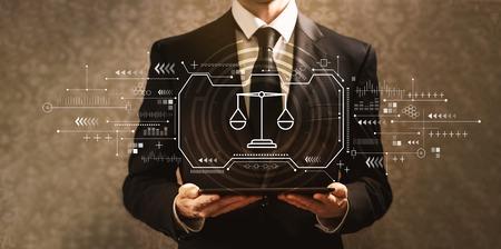 Foto de Justice theme with businessman holding a tablet computer - Imagen libre de derechos
