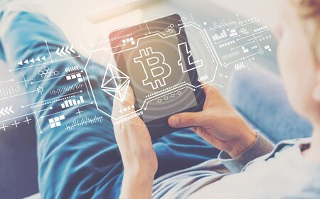 Foto de Cryptocurrency - Bitcoin, Ethereum, Litecoin with man using a tablet in a chair - Imagen libre de derechos
