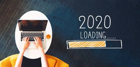 Foto per Loading new year 2020 with person using a laptop on a white table - Immagine Royalty Free
