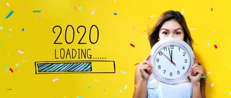Photo pour Loading new year 2020 with young woman holding a clock showing nearly 12 - image libre de droit