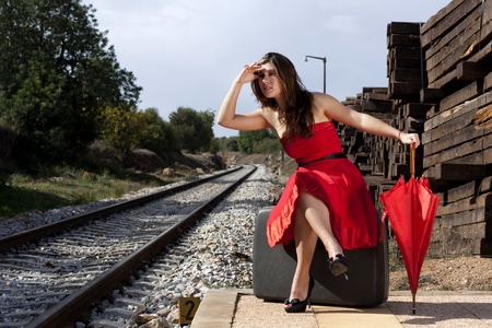 View of a beautiful woman with red dress and umbrella on a train station.