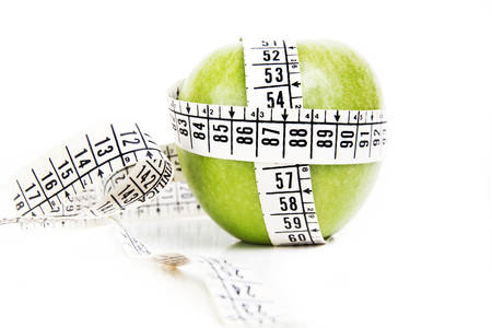 Foto de Green apple with a measuring tape around - Imagen libre de derechos