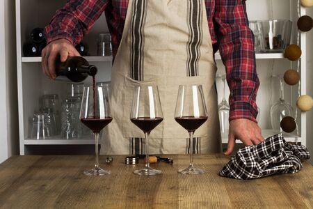 Photo pour Man with an apron serving a glass of red wine - image libre de droit
