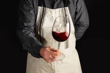 Photo pour A man with an apron and a glass of red wine in is hand - image libre de droit