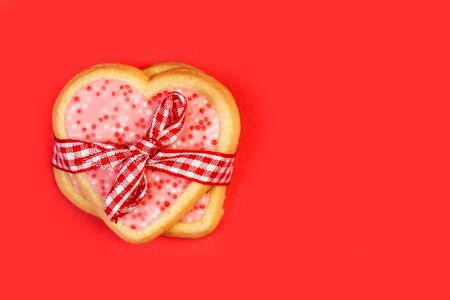 Foto de Heart shape cookies with a red and white checked ribbon on a red background - Imagen libre de derechos