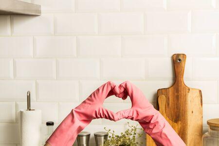 Foto de Woman showing heart shape with hands in the kitchen - Imagen libre de derechos