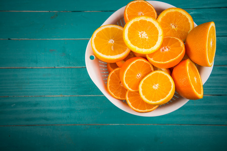 Photo for Fresh orange halves on rustic wooden kitchen table - Royalty Free Image