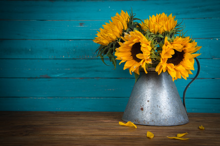 Foto de Fresh sunflower flowers in rustic antique vase on wooden table and rustic background - Imagen libre de derechos