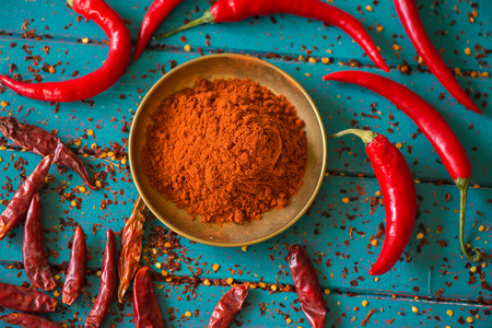Photo pour Chilli powder and fresh and dried peppers on table background - image libre de droit