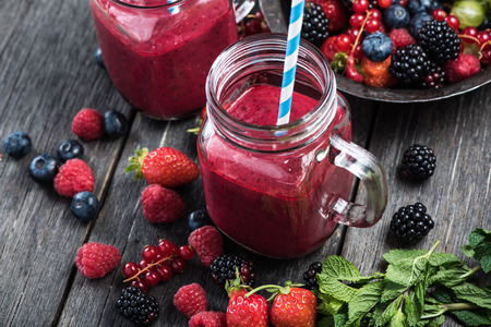 Photo for Summer berries smoothie in mason jar on rustic wooden table - Royalty Free Image