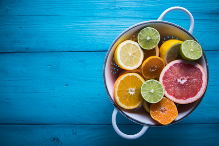 Photo for Vibrant citrus half cut fruits on wooden table - Royalty Free Image